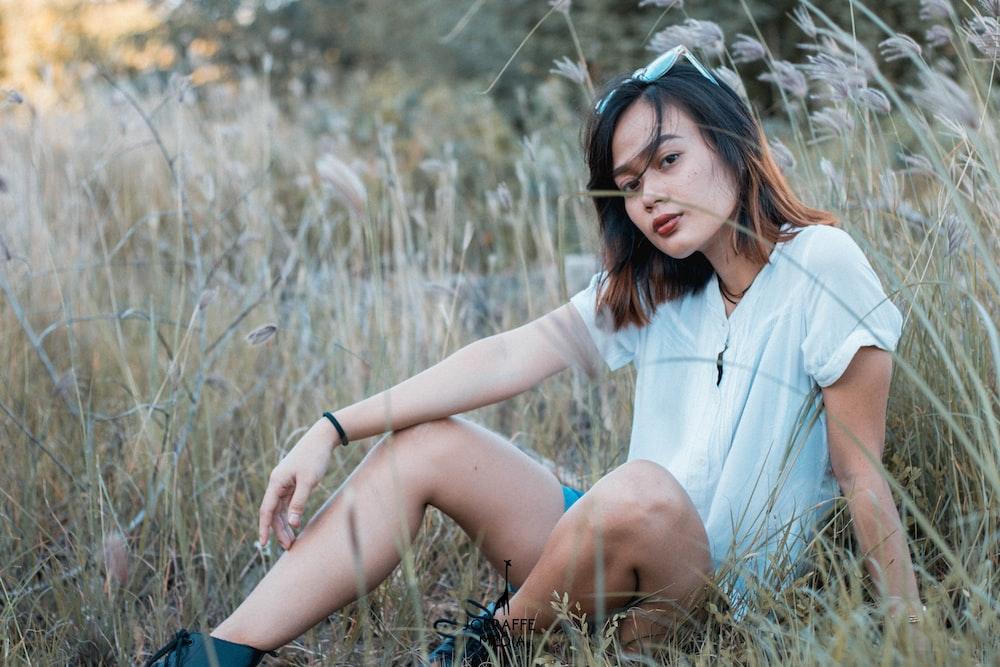 woman sitting on grass field