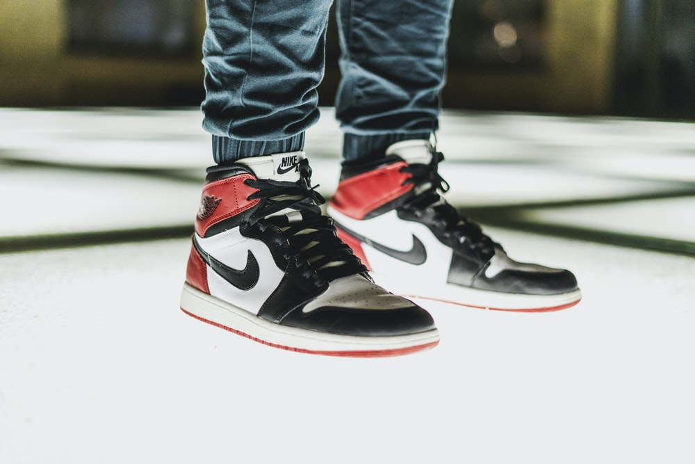 person wearing black-white-and-red Air Jordan 1's