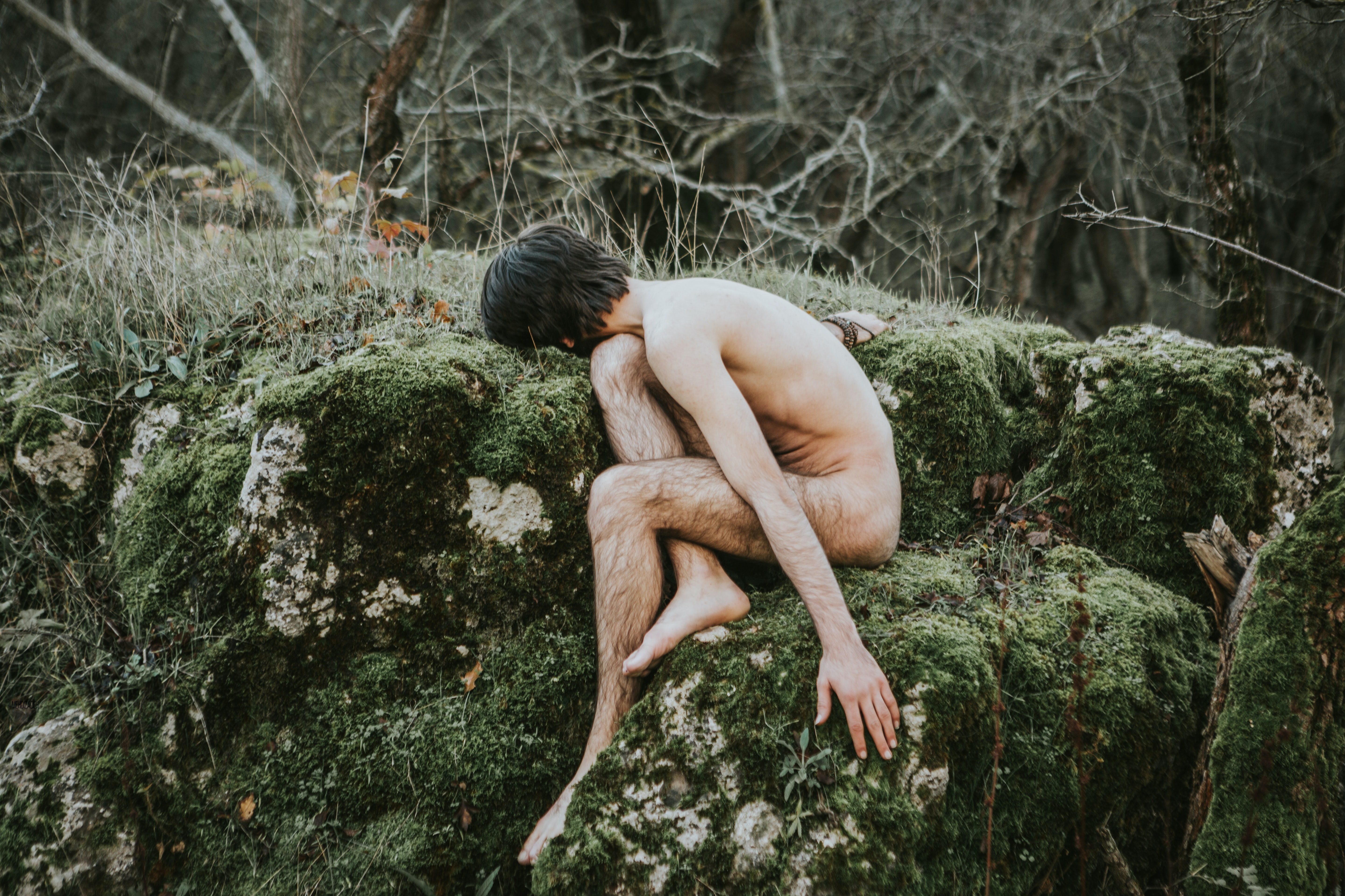 naked person sitting on green grass