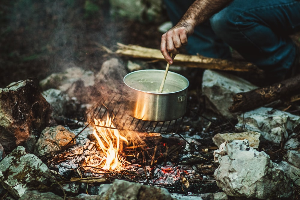 person cooking on bonefire