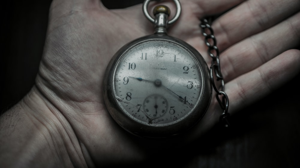 person holding pocket watch pointing on 9:20