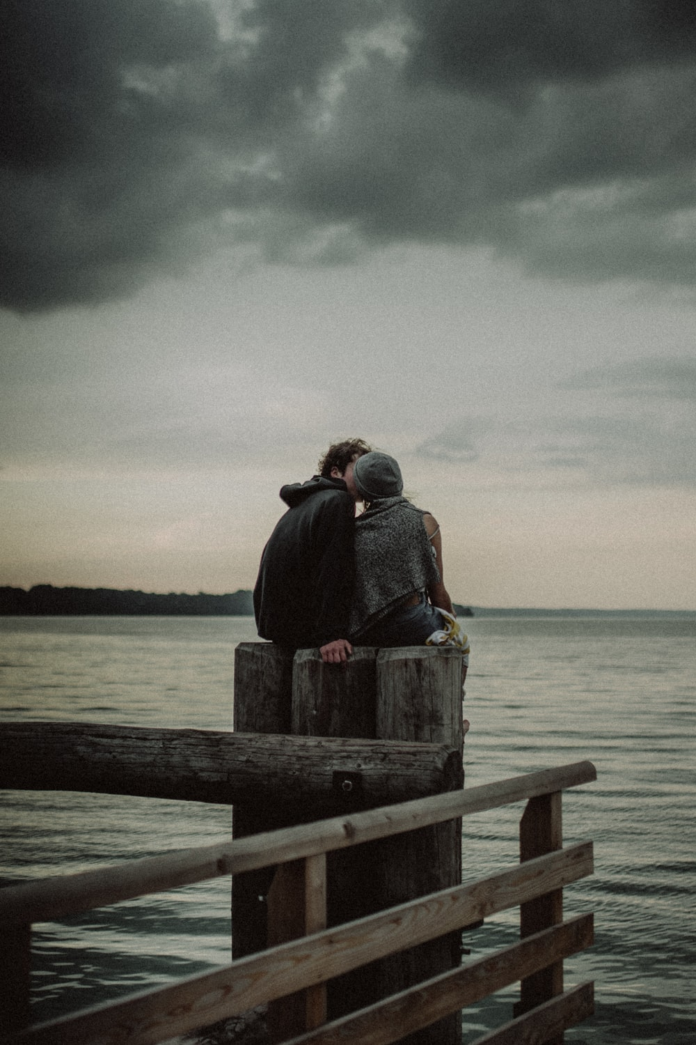 man and woman sitting and kissing on post near the body of water