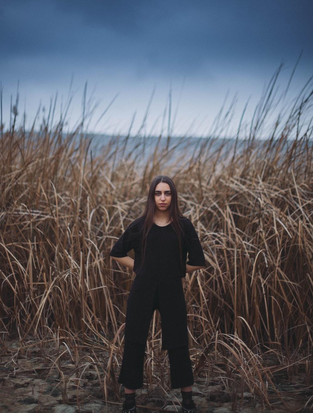 woman standing near brown grass field