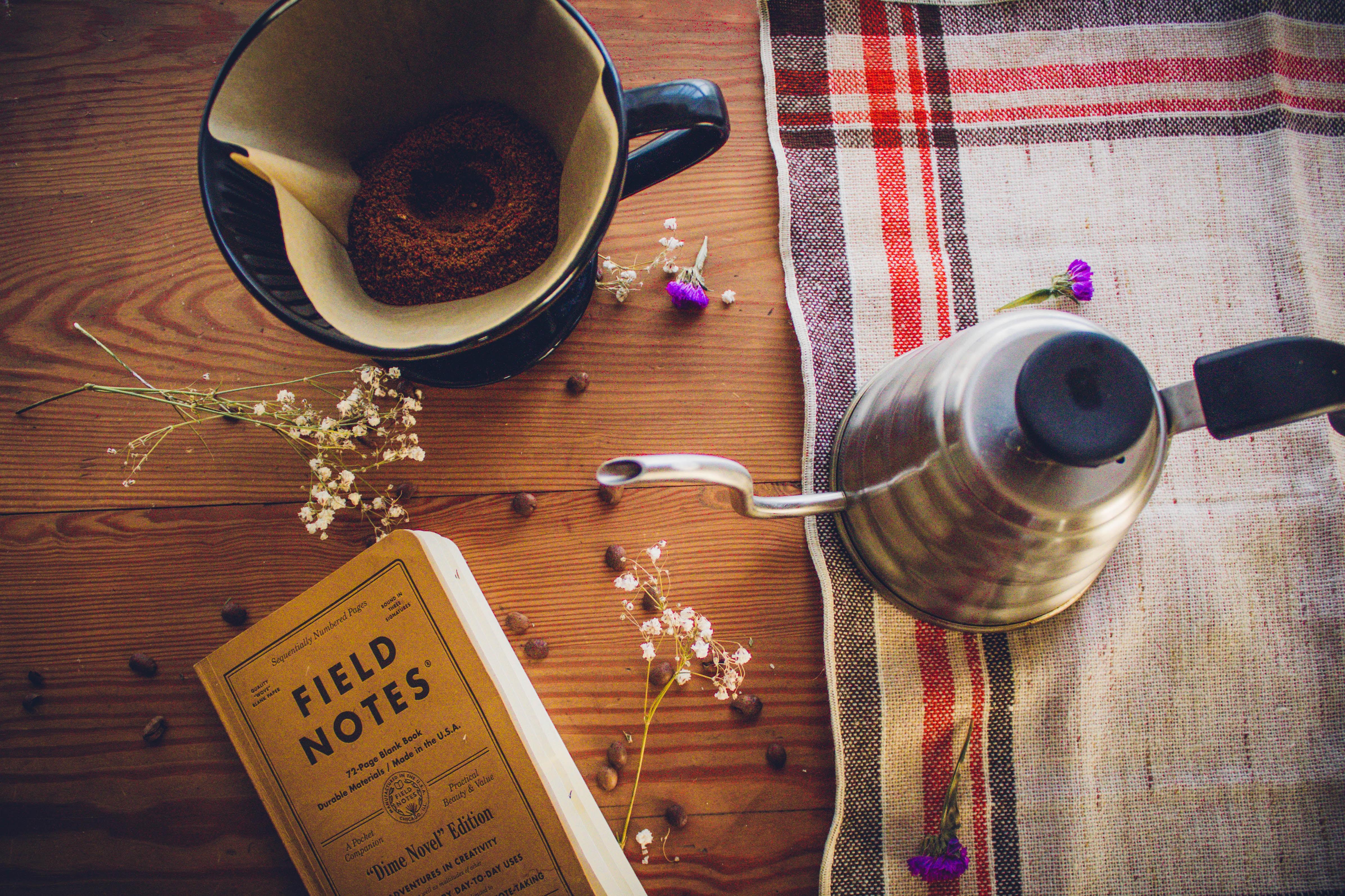 Field Notes book near coffee mug and teapot