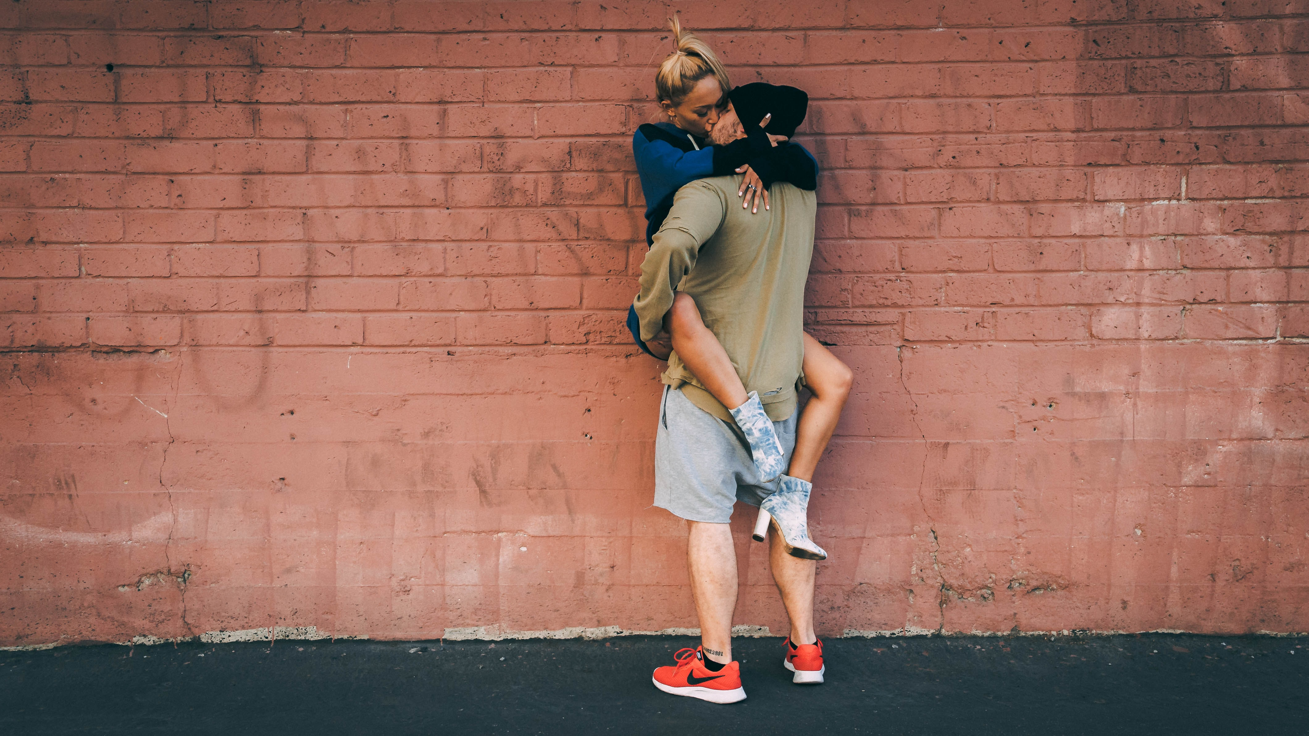 man carrying woman while kissing beside wall