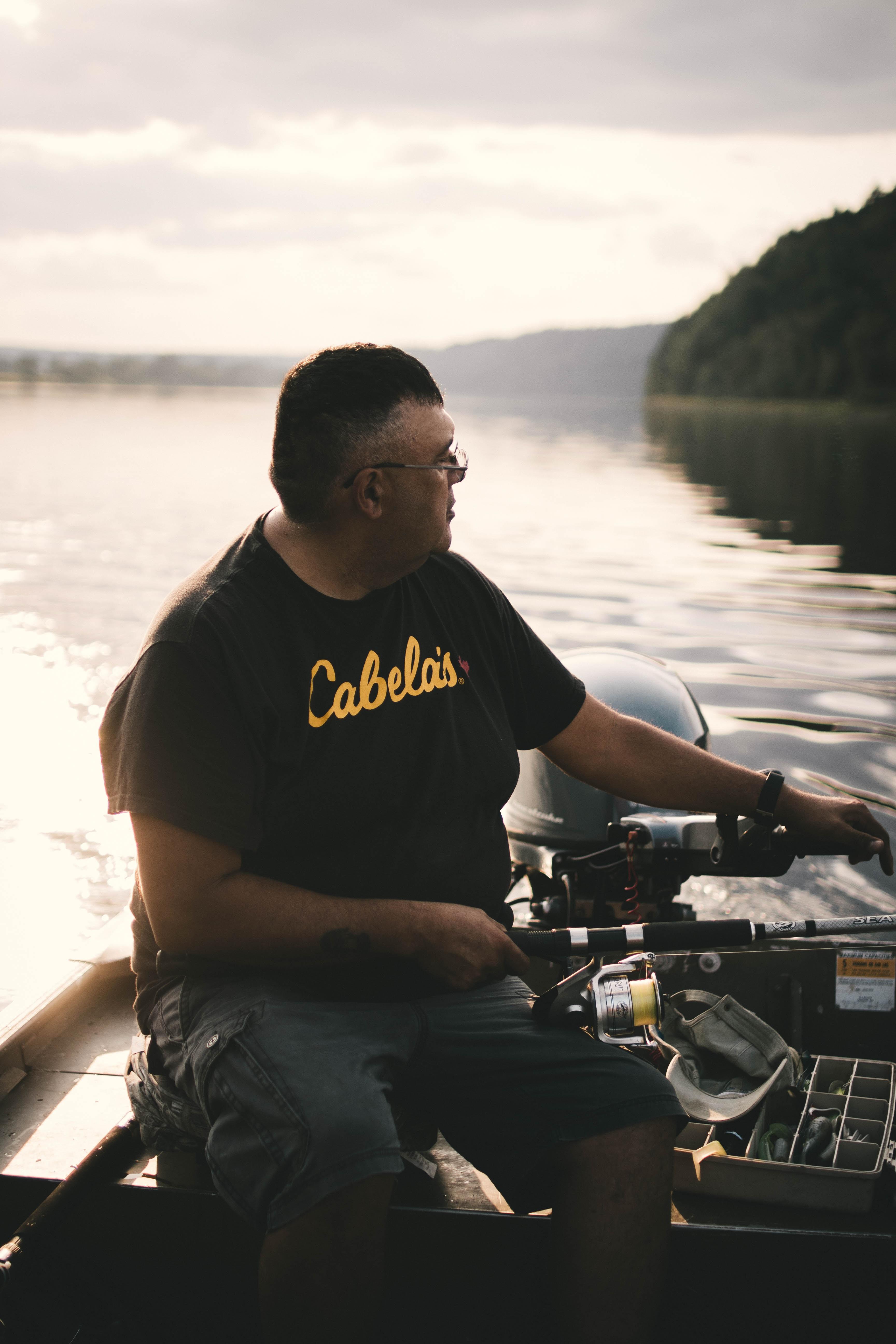 man on boat holding fishing rod