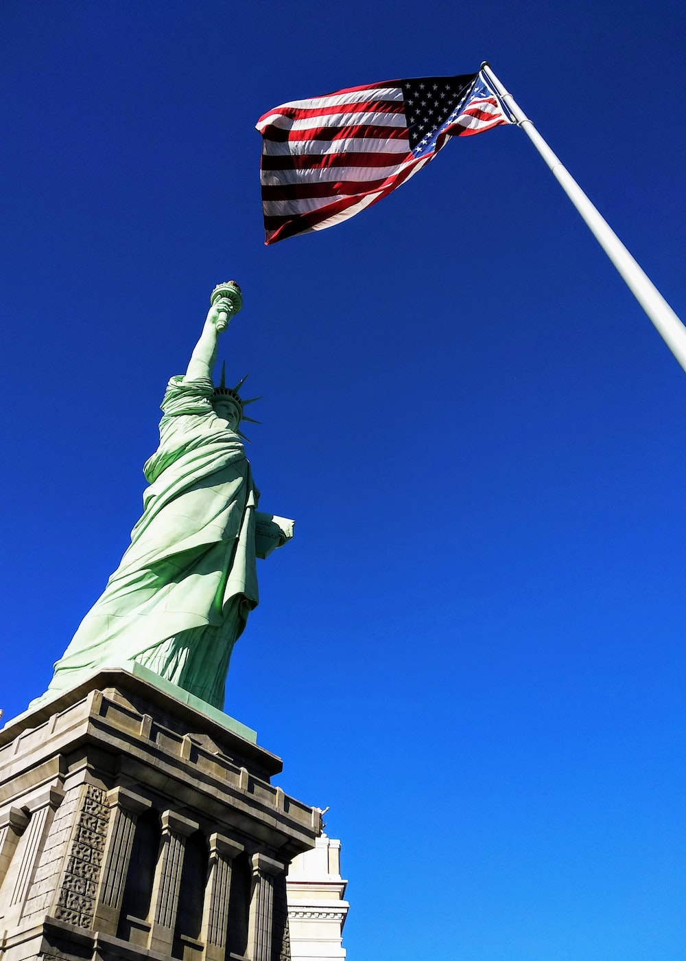 Statue of Liberty in front USA flag under blue sky