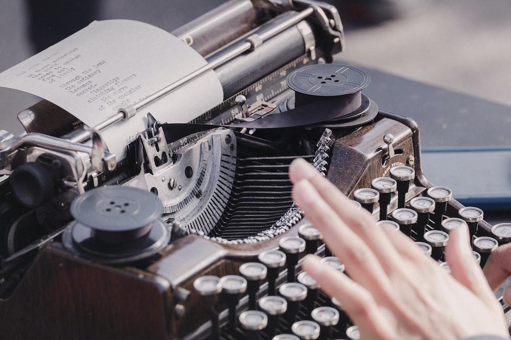 person typing using typewriter