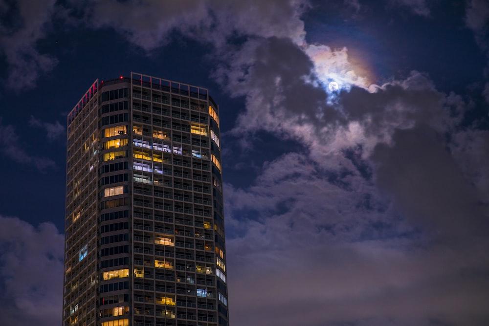 high rise building under cumulus clouds