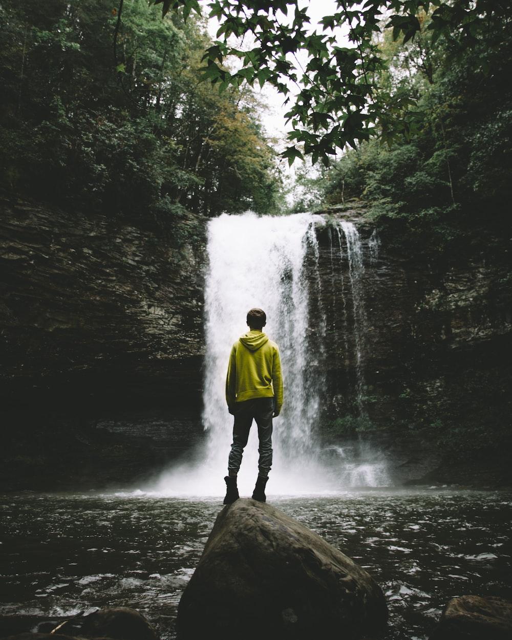 man standing on rock looking at waterfalls
