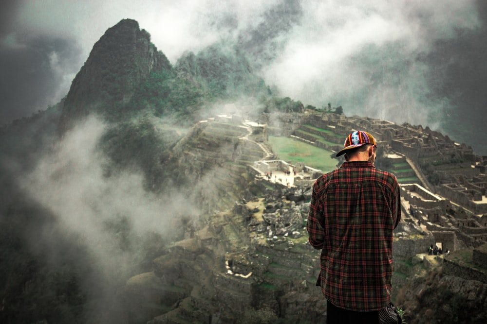 man standing on cliff facing mountain rice terraces