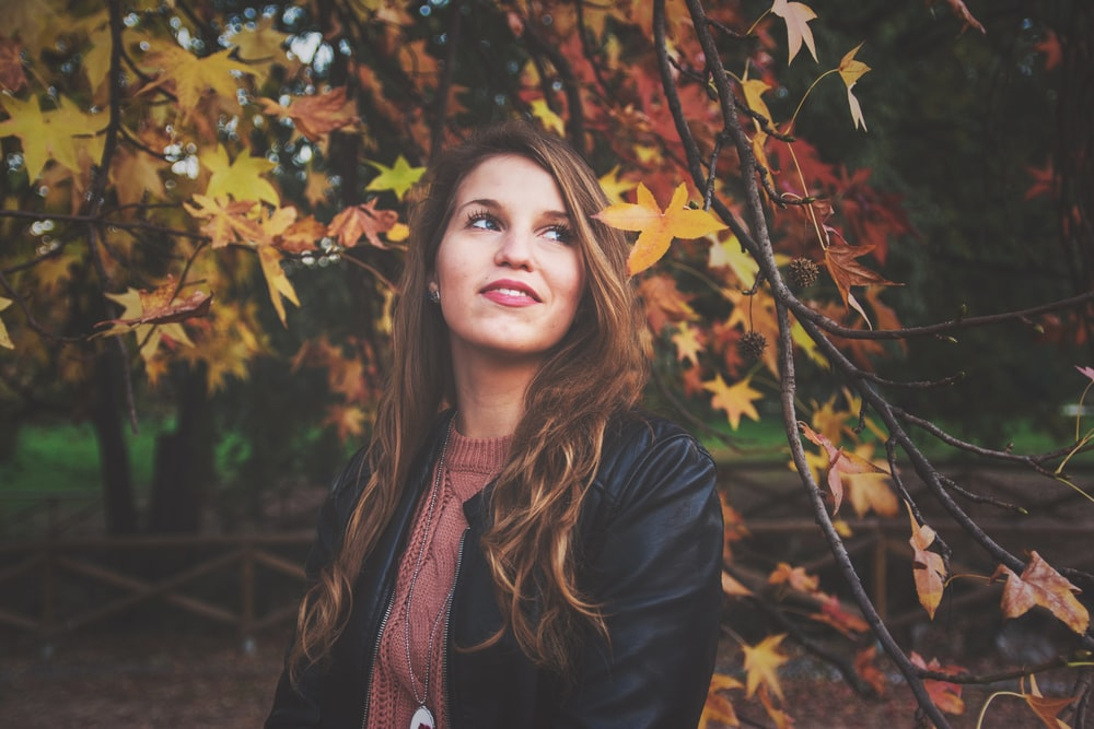 woman beside maple leaf tree