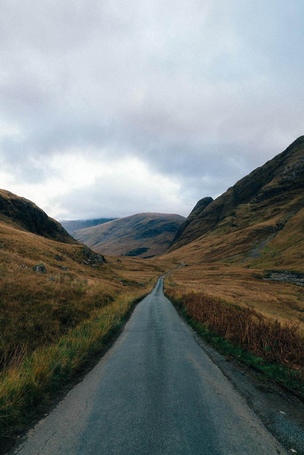 empty road between brown mountains under blue sky