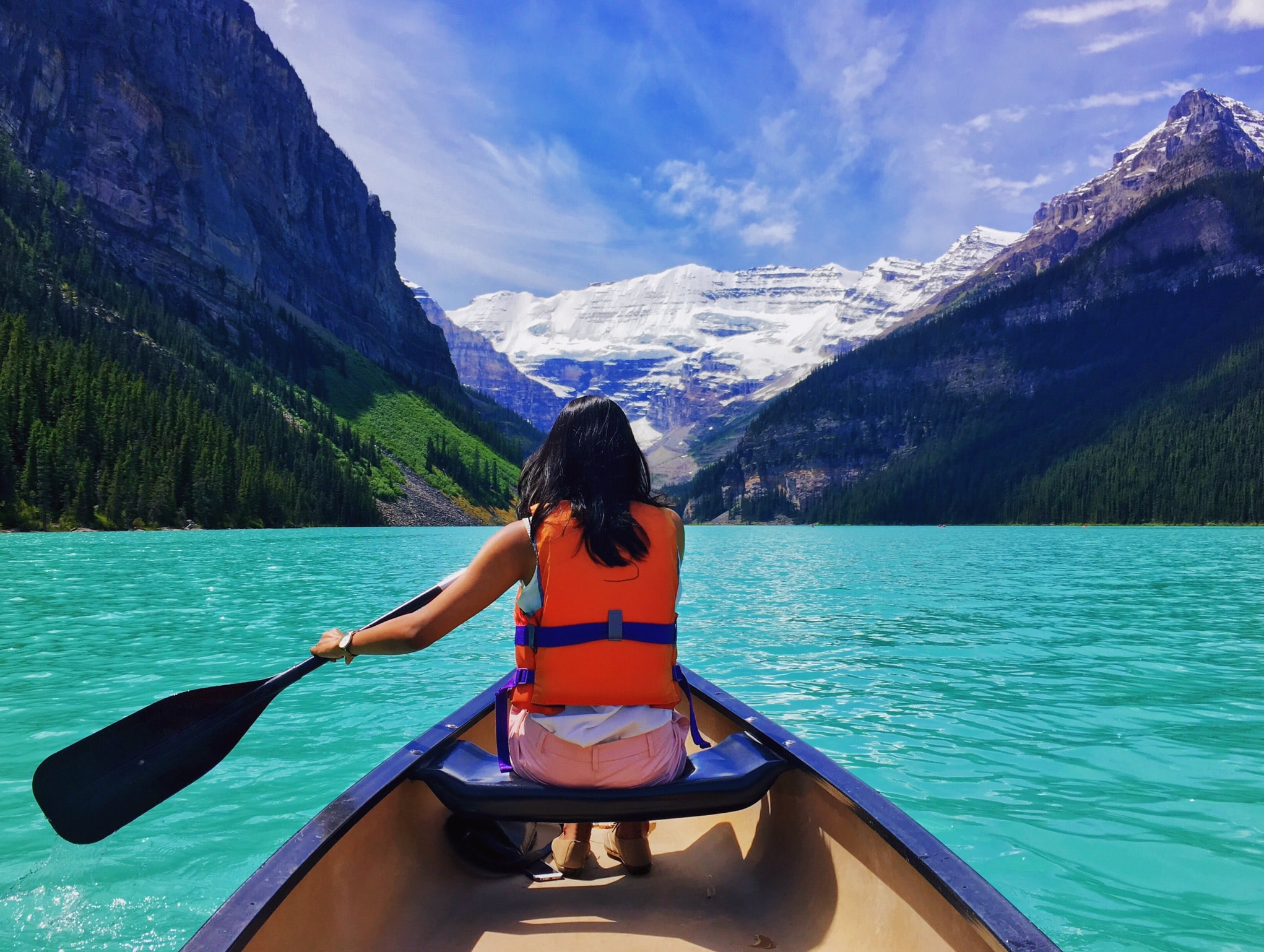 woman rowing riding a boat near mountains