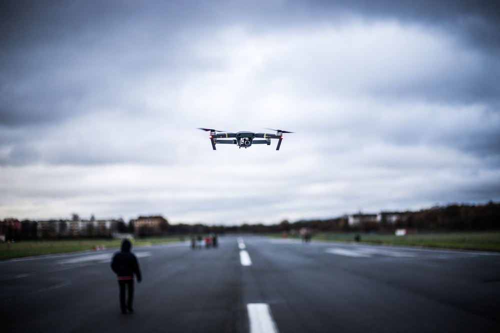 white drone flying near road