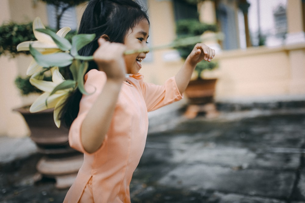 girl holding a yellow flower while running
