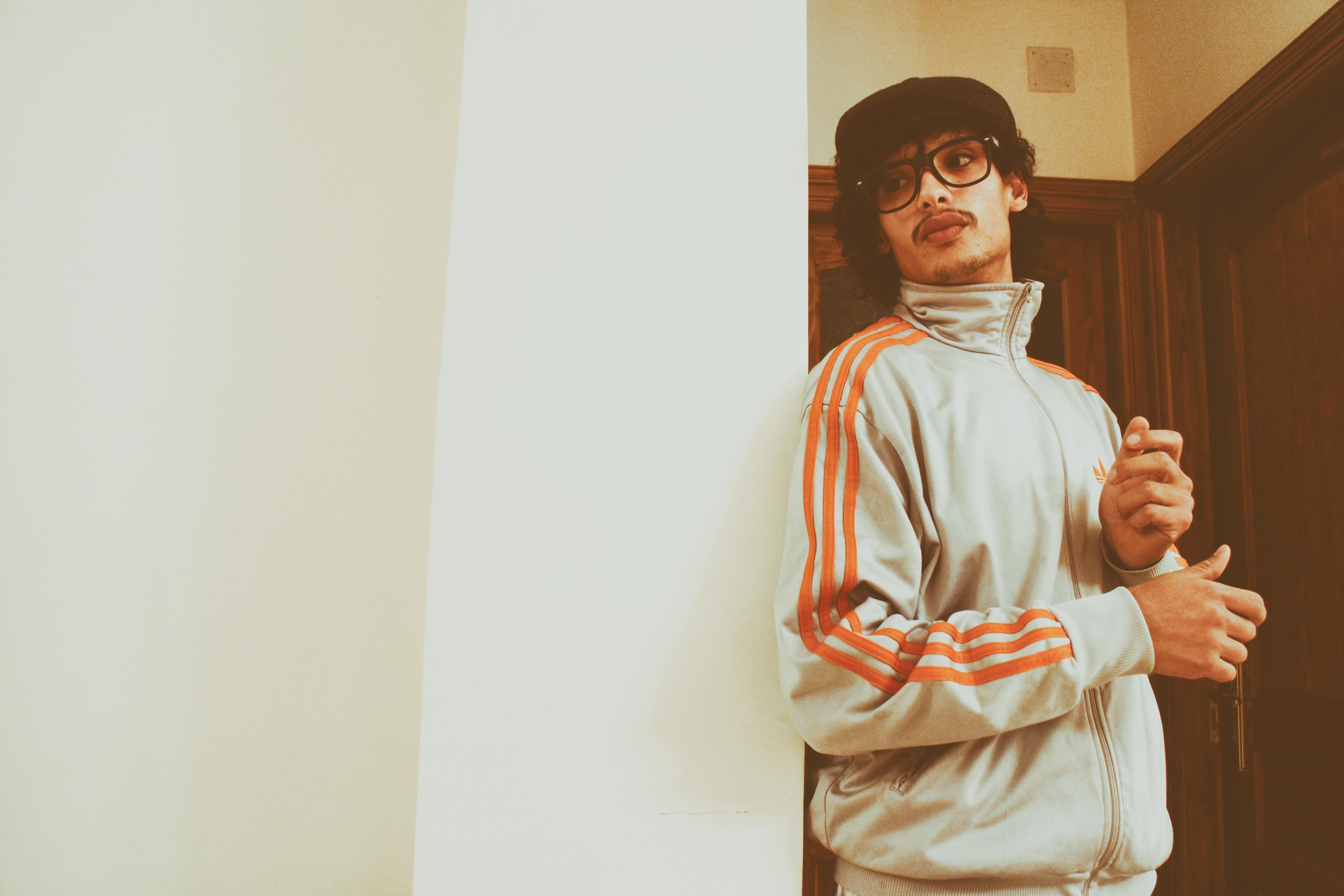 man wearing Adidas jacket leaning on wall