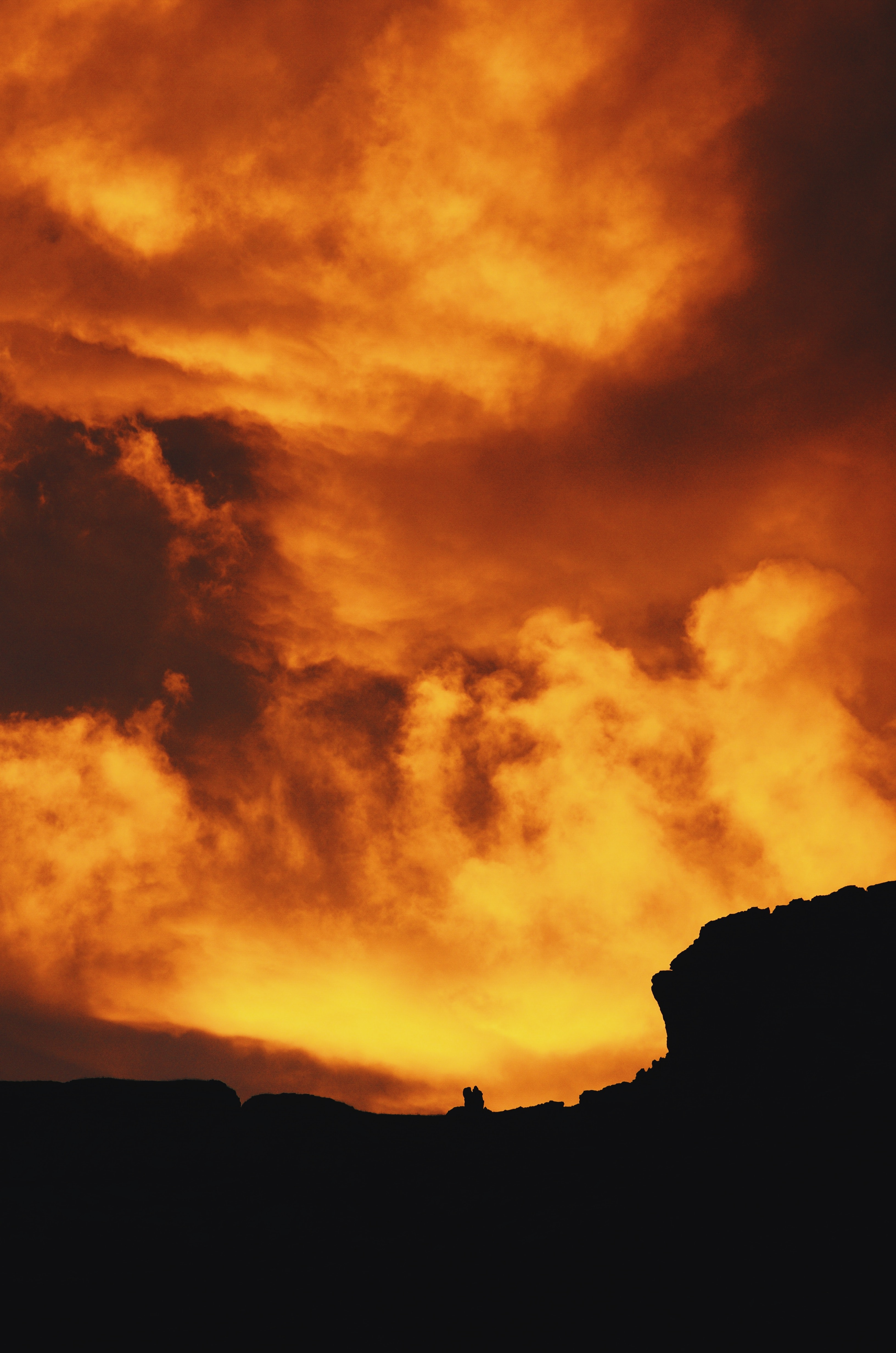 silhouette photography of hill under red sky