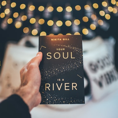 person holding a Your Soul novel book