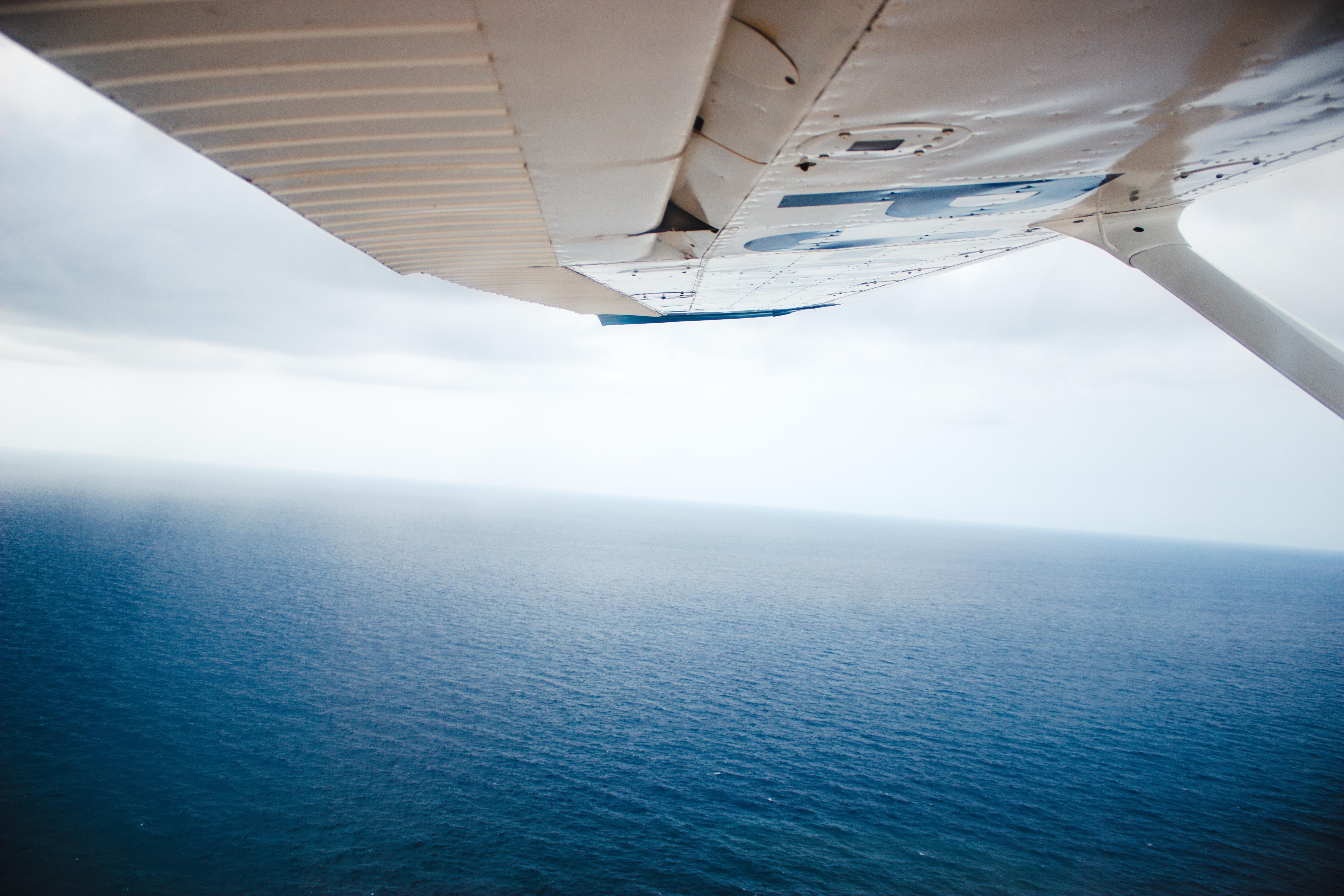 aerial photography of plane flying above ocean