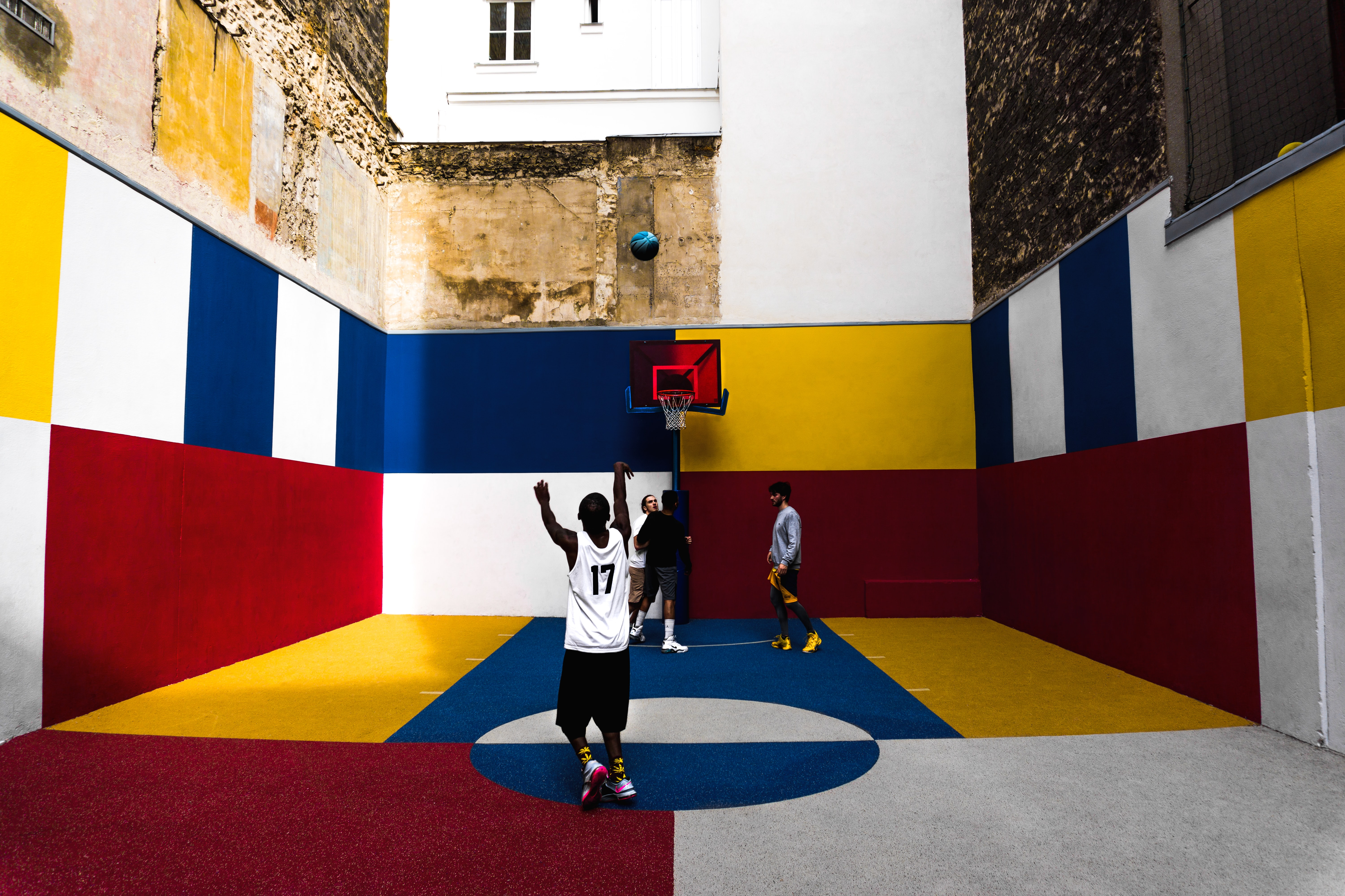 man playing basketball inside multicolored court