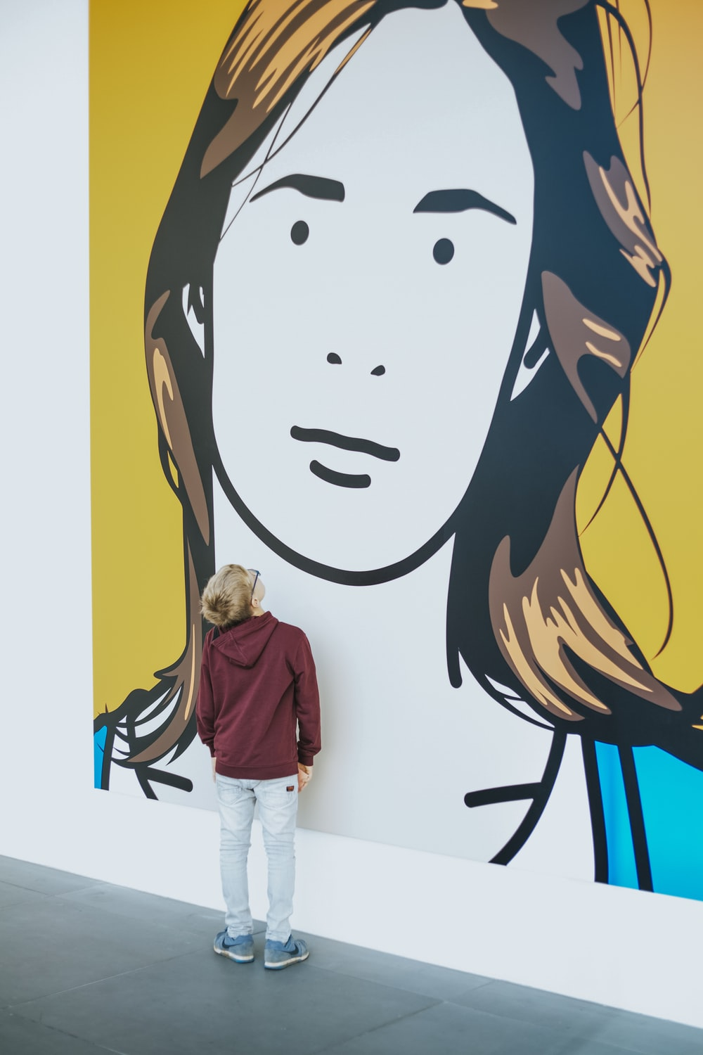 boy standing and facing woman wall painting