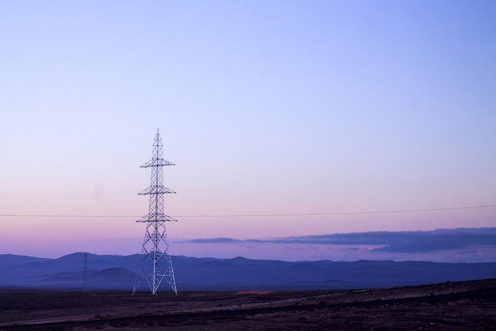 landscape photography of electricity pylon on field