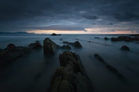 rock formations on body of water under cloudy sky