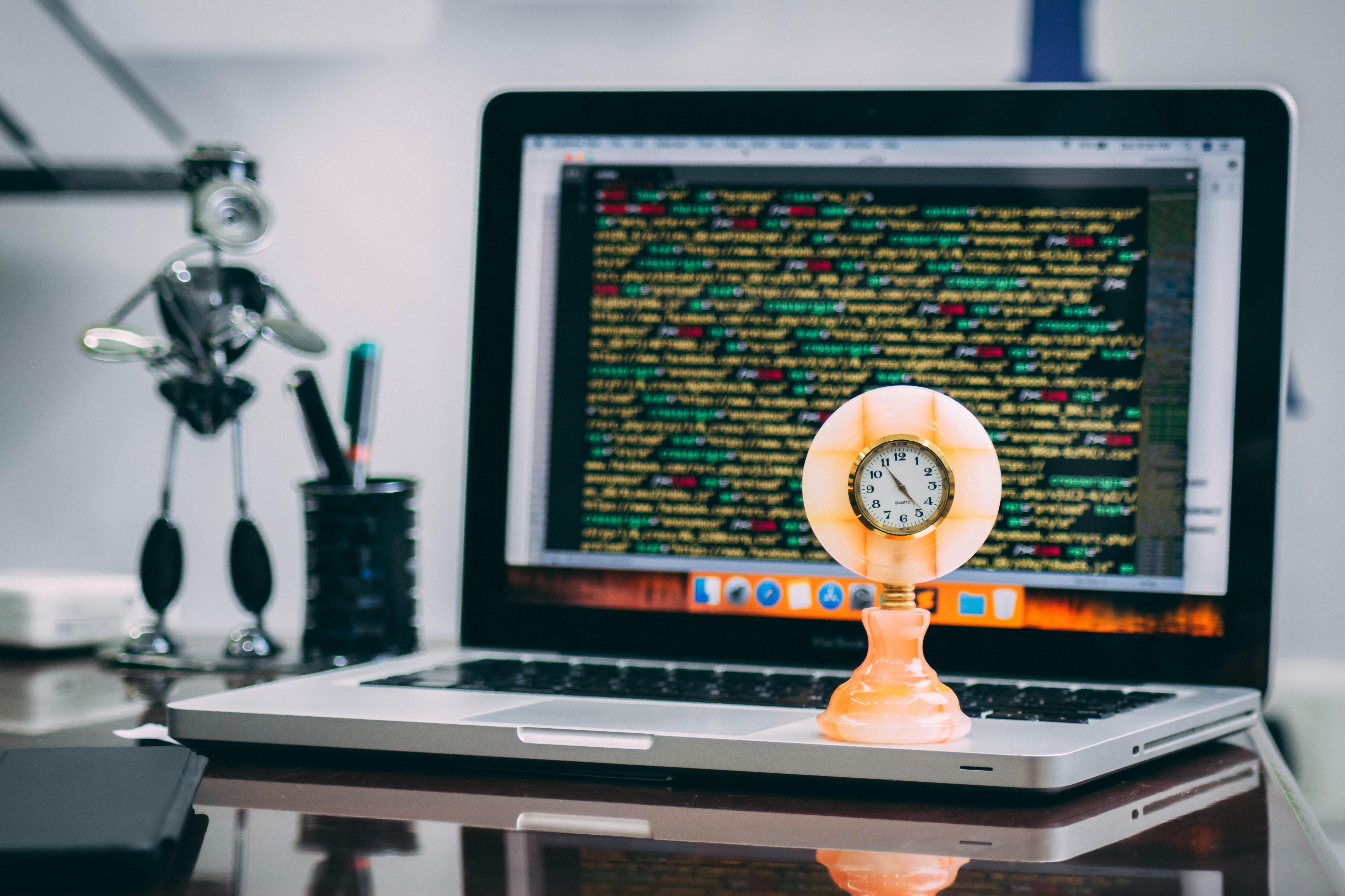 round beige analog table clock on MacBook Pro