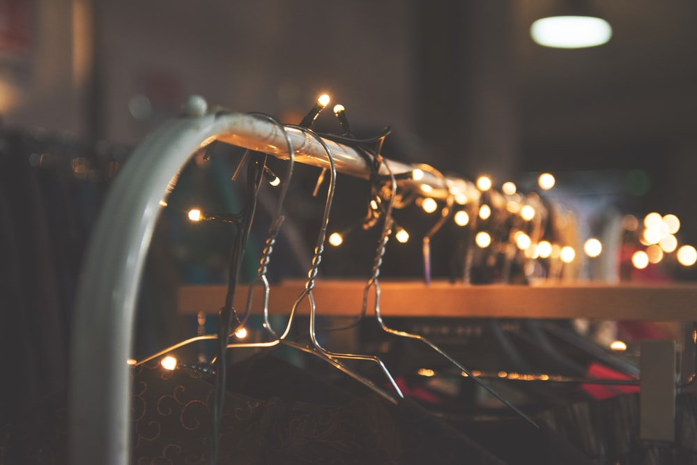 silver clothes hangers with string lights
