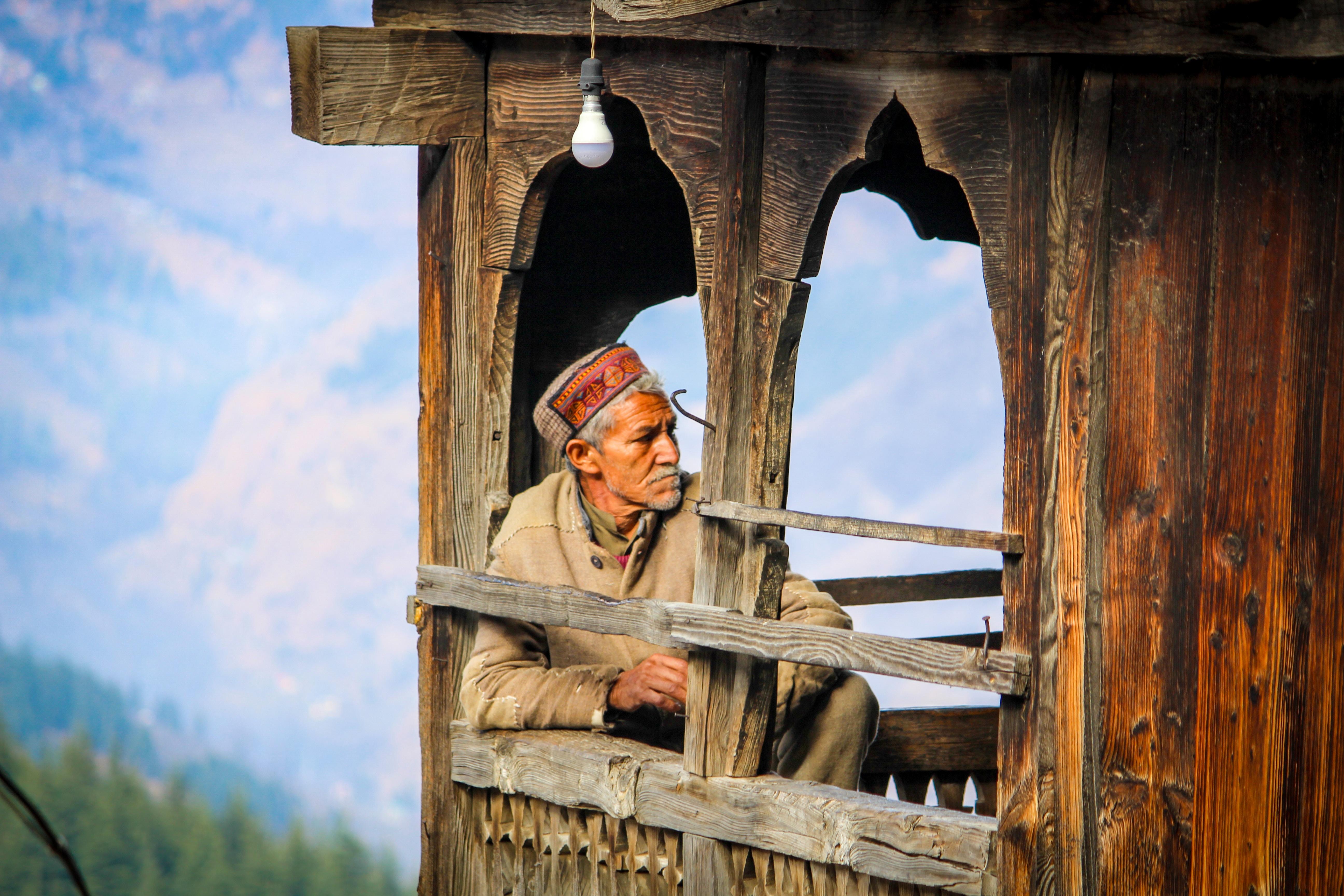 sitting man inside brown wooden building