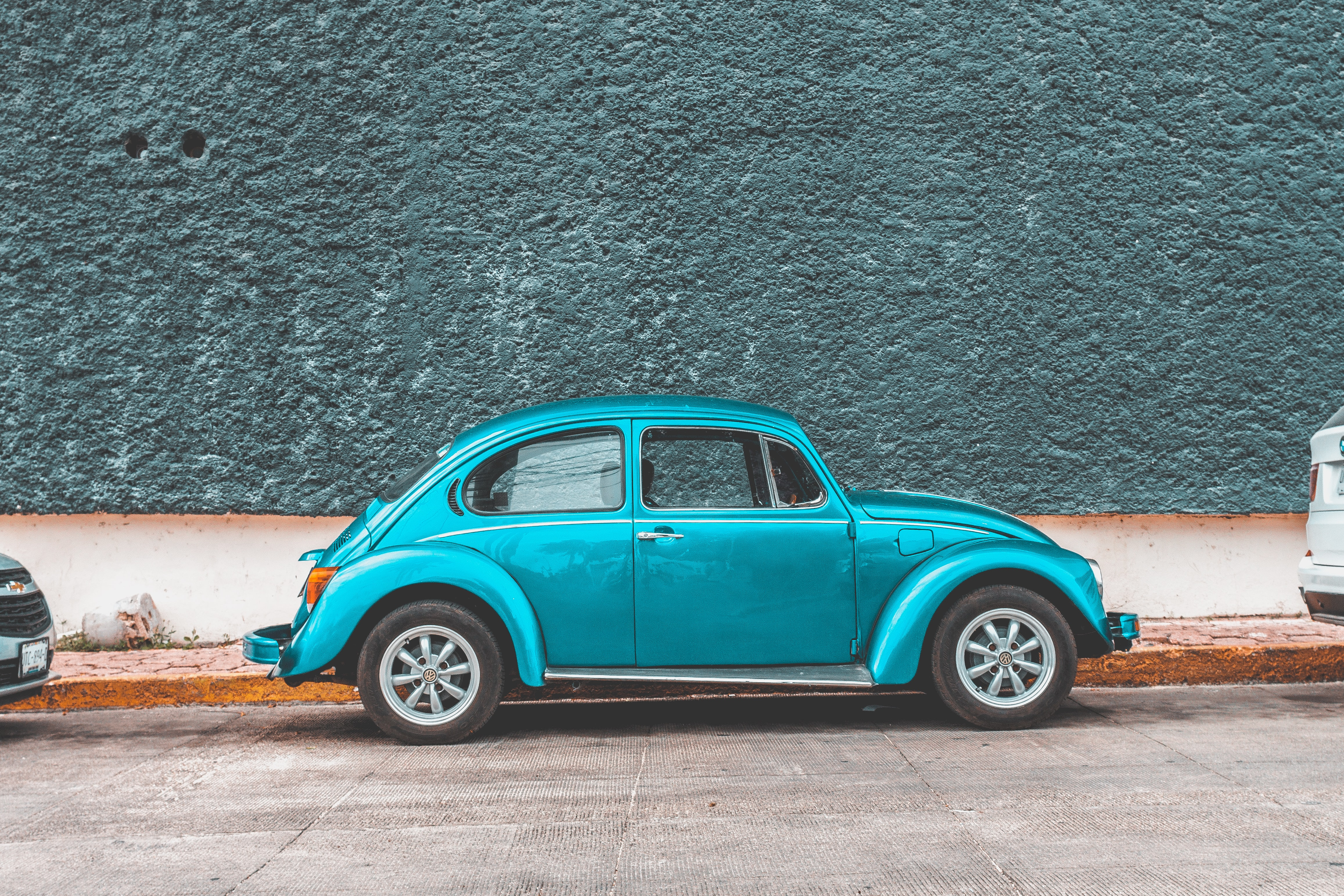 teal Volkswagen Beetle car parked beside sidewalk