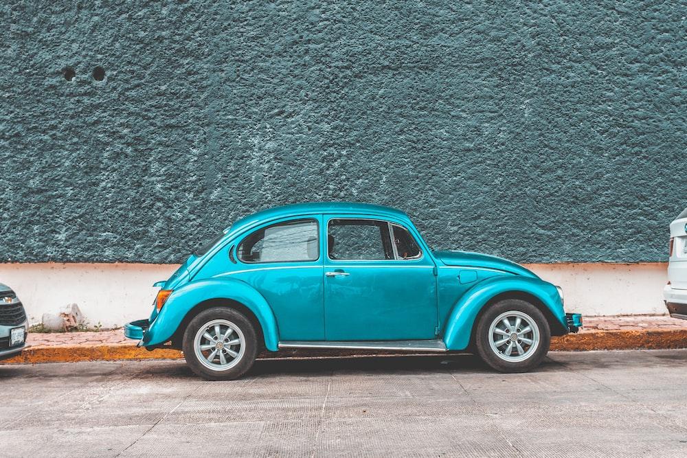 teal Volkswagen Beetle car parked beside sidewalk