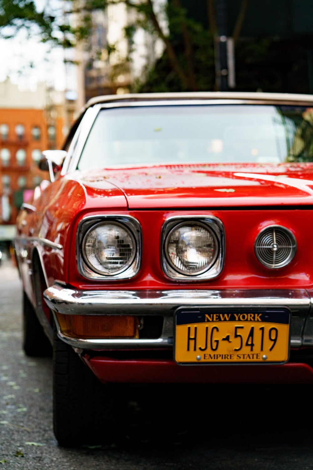 close up photo of red car with New York HJG 5419 license plate