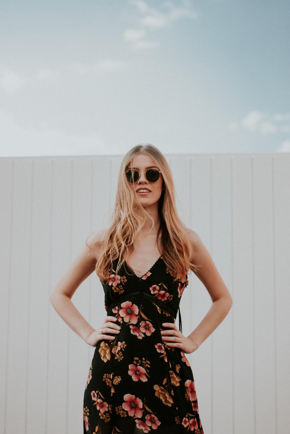 woman wearing black sunglasses standing near white wooden wall