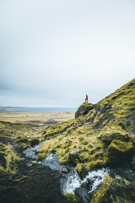 man standing on green mountain during daytime