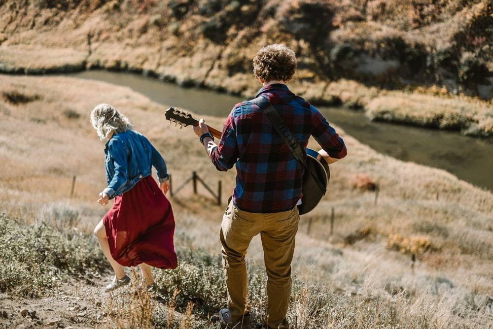 man playing guitar standing behind woman on mountain