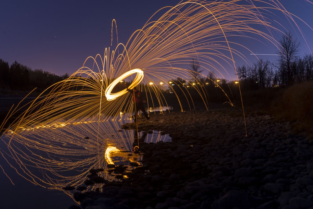 time-lapse photography of person holding lighted steel wool at night