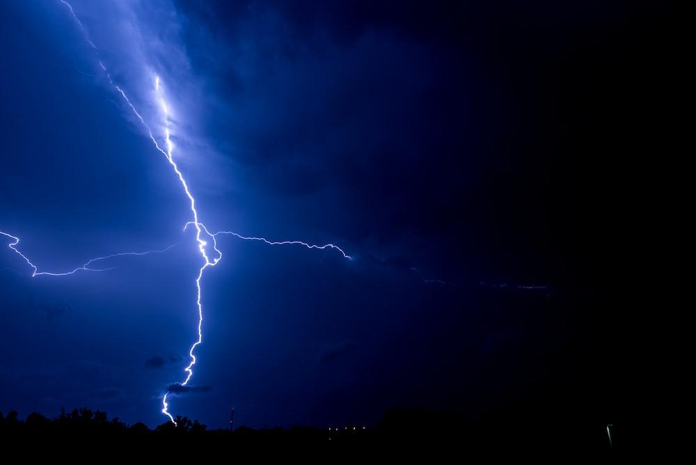 lightning bolts striking a body of land during night