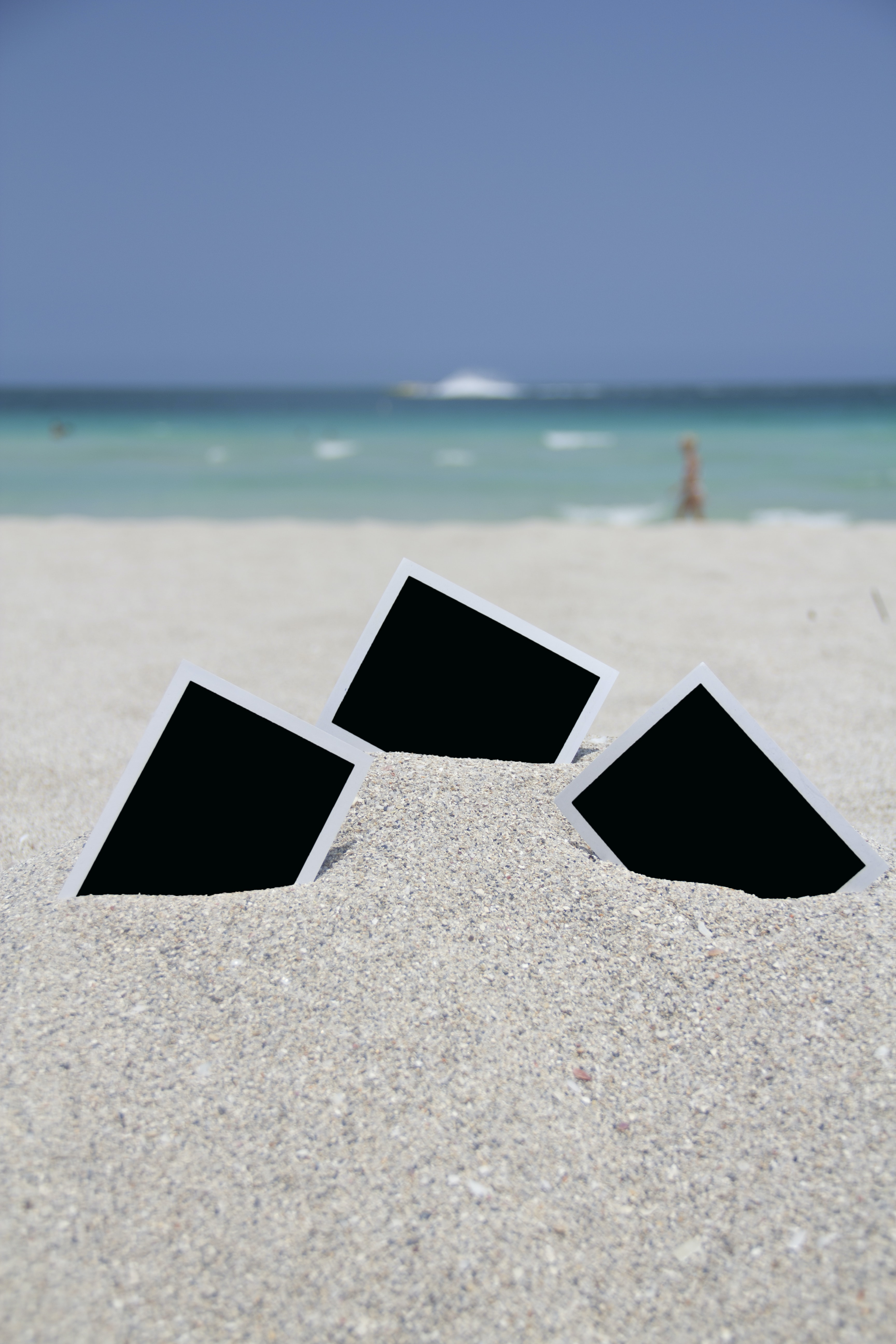 three photo frames on seashore near sea