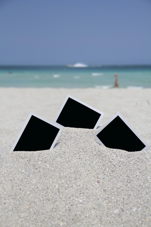 three photo frames on seashore near sea