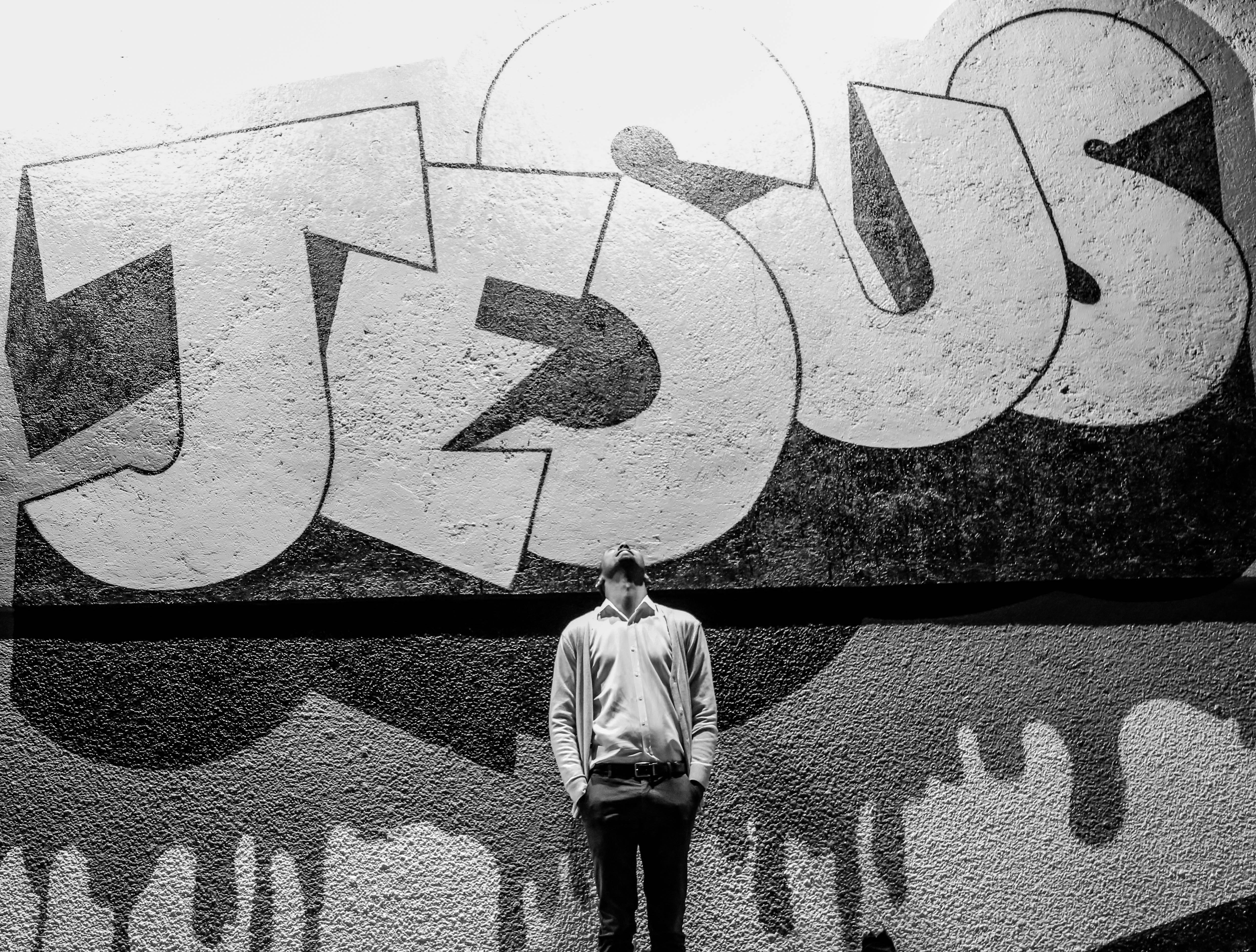 grayscale photography of a man standing in front of a Jesus graffiti