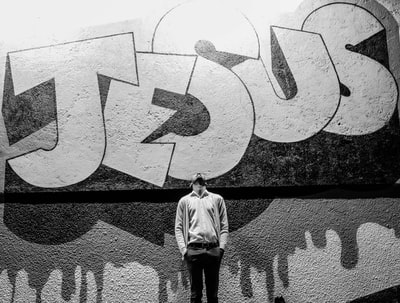 grayscale photography of a man standing in front of a jesus graffiti jesus teams background