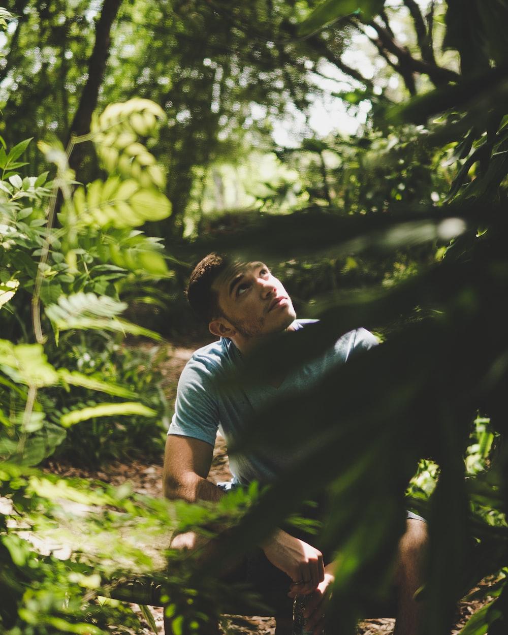 man sitting beside green trees during daytime