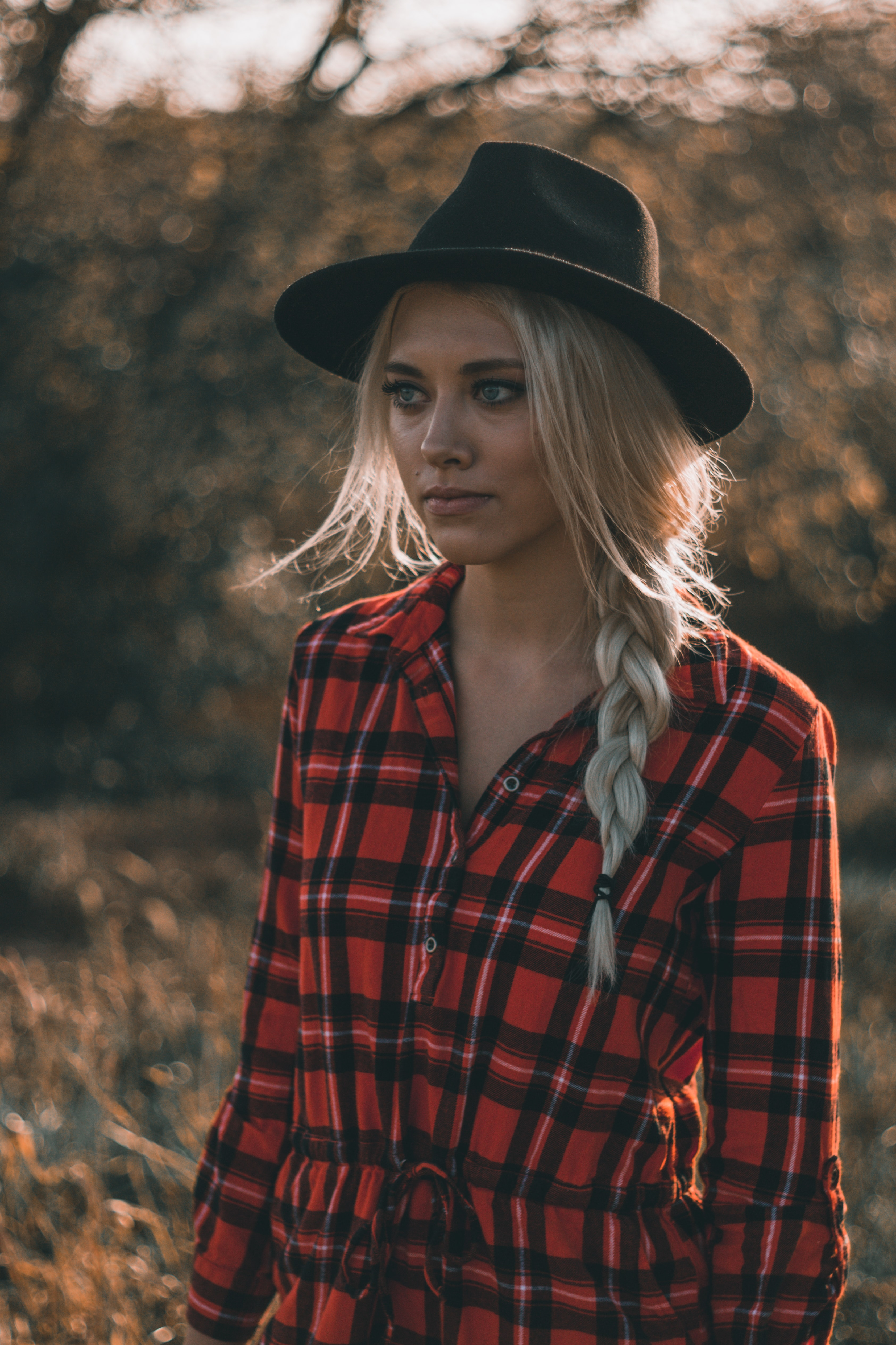 bokeh photography of woman wearing trilby hat and sports shirt