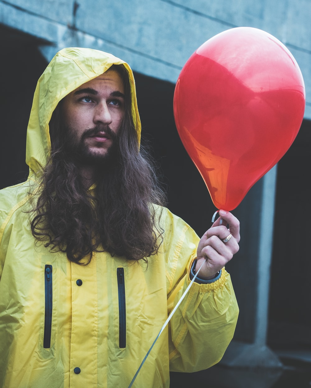 man holding red balloon
