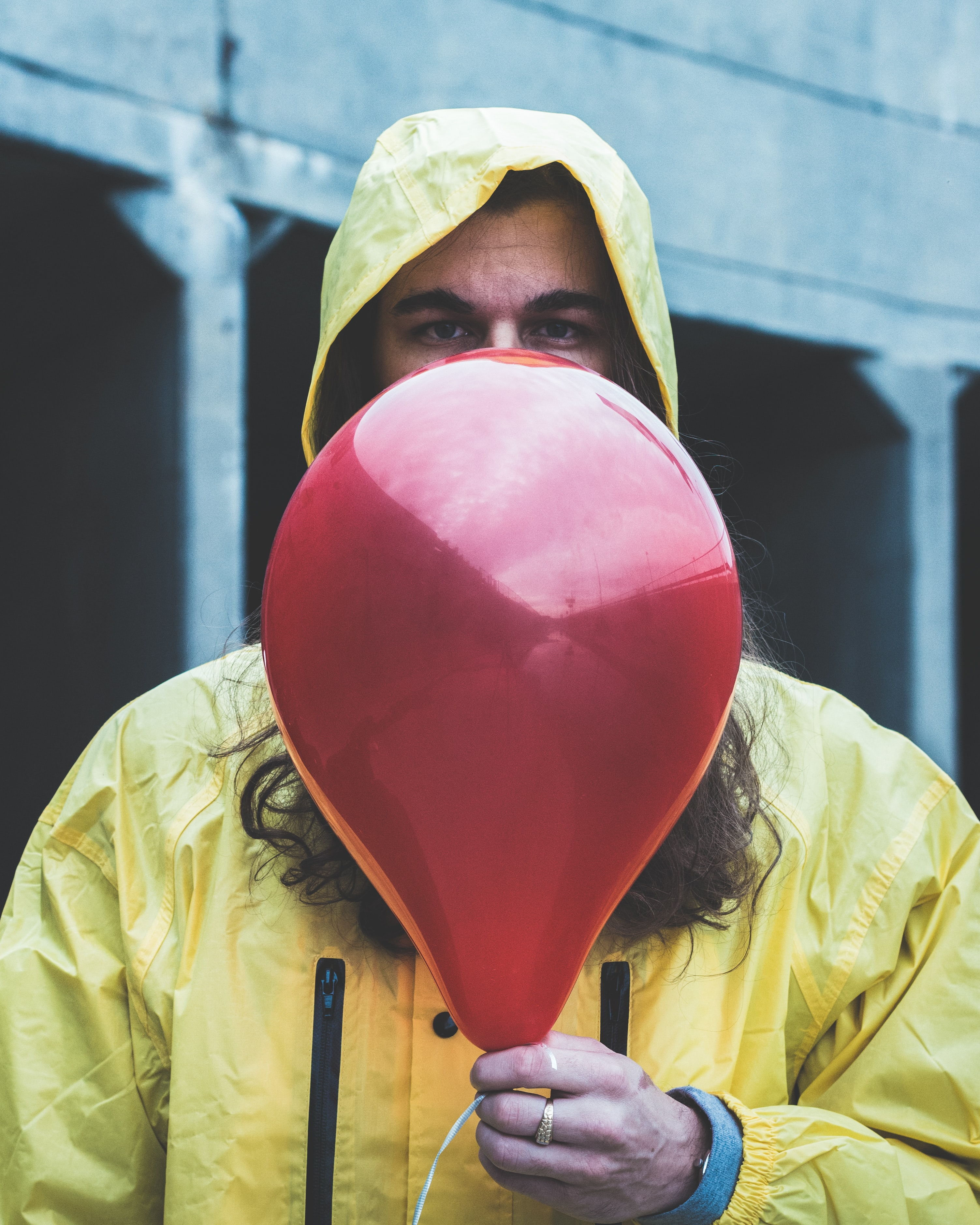 person on raincoat holding red balloon