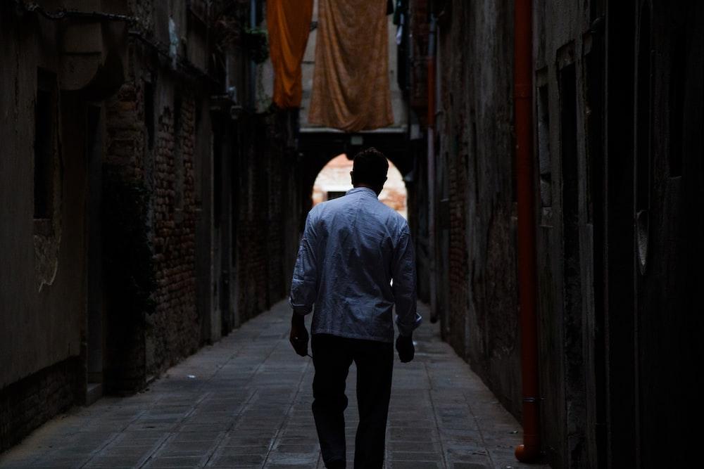 man standing between brown concrete building