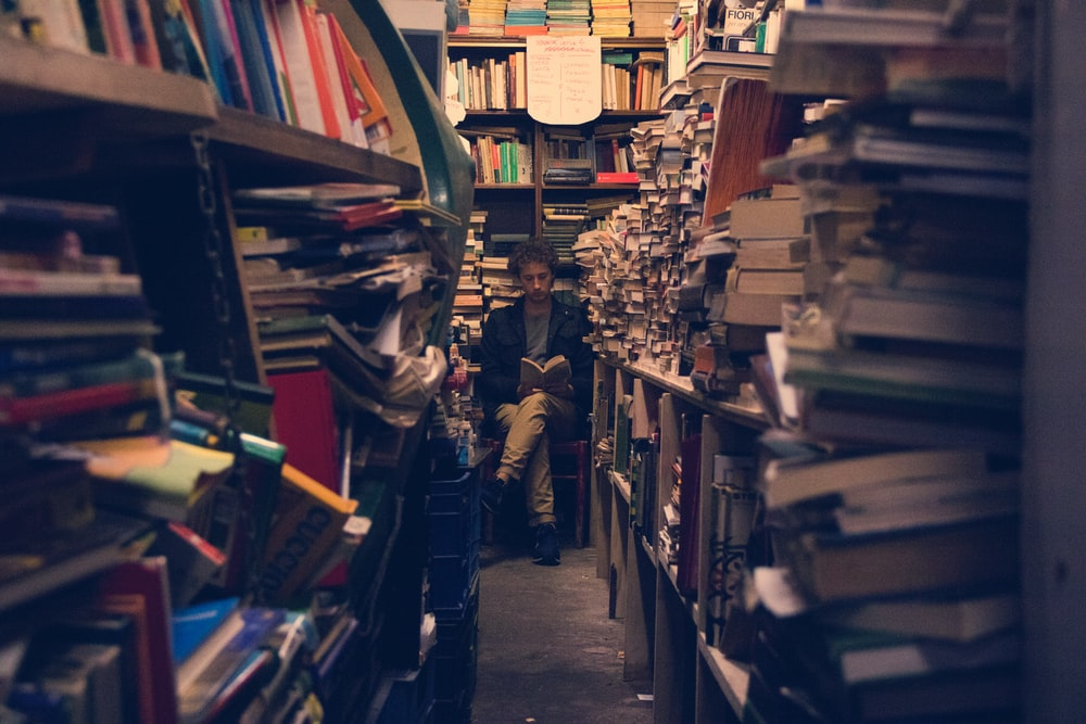 man sitting reading book on the end of pile of book racks