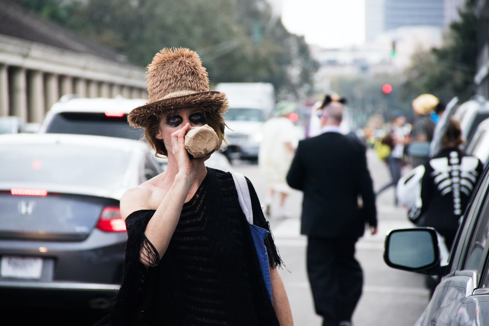 woman drinking from bottle while standing near traffic